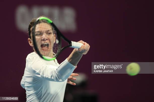 TOPSHOT Simona Halep of Romania returns the ball to Elina Sitolina of Ukraine during their WTA Qatar Open semifinal tennis match in Doha on February...