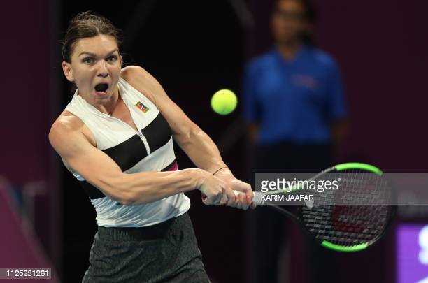 Simona Halep of Romania returns the ball to Elise Mertens of Belgium during the third set of their WTA Qatar Open final tennis match in Doha on...