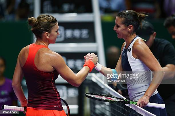Simona Halep of Romania shakes hands with Flavia Pennetta of Italy after defeating her in a round robin match during the BNP Paribas WTA Finals at...