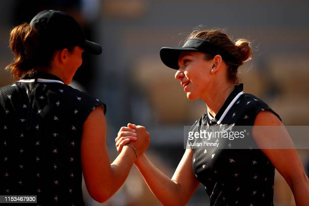 Simona Halep of Romania shakes hands with Iga Swiatek of Poland after their ladies singles fourth round match during Day nine of the 2019 French Open...