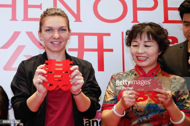 Simona Halep of Romania shows her paper cutting of the Chinese character 'Xi' meaning double happiness ahead of the 2018 WTA Shenzhen Open on...