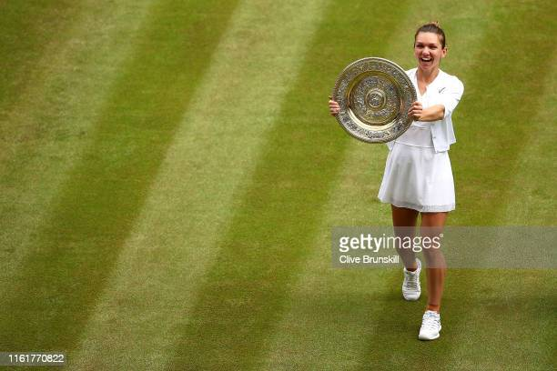 Simona Halep of Romania shows off the trophy after winning the Ladies' Singles final against Serena Williams of The United States during Day twelve...