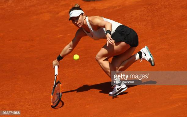 Simona Halep of Romania stretches to play a forehand against Ekaterina Makarova of Russia in their first round match during day two of the Mutua...
