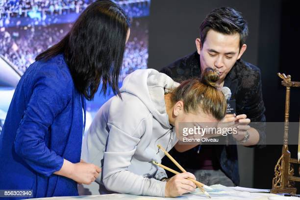 Simona Halep of Romania writes with a brush during an event at the Mercedes-Benz booth during day two of the 2017 China Open at the China National...