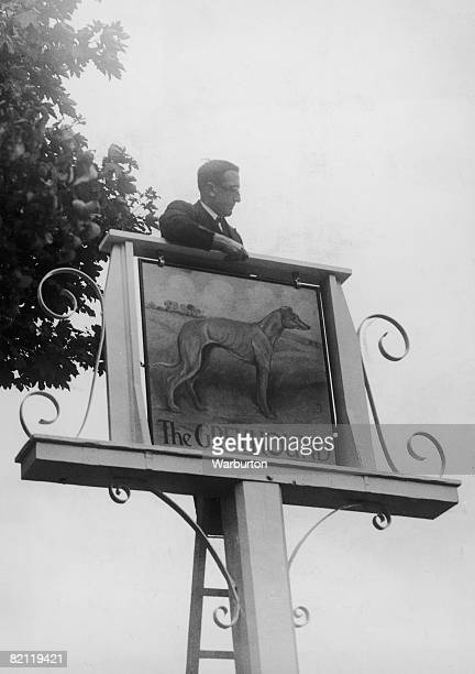 J B Simonds Director of the Young Co Brewery hangs a new sign outside 'The Greyhound' an old coaching inn in Carshalton Surrey 20th August 1948