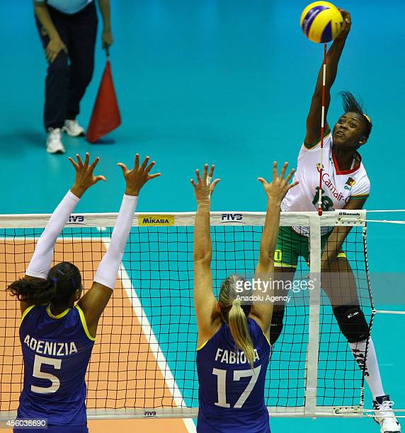 Simone Bikatal of Cameroon in action against Adenizia and Fabiola of Brazil during the 2014 FIVB Volleyball Women's World Championship Group B match...