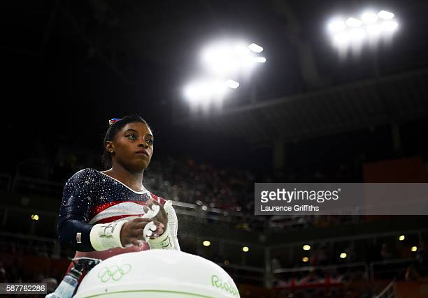 Simone Biles of the United States applies chalk in preparation for competing on the uneven bars during the Artistic Gymnastics Women's Team Final on...