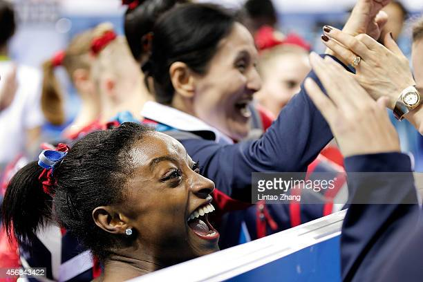 Simone Biles of the United States celebrates after team win the gold medal of the Women's Team Final on day two of the 45th Artistic Gymnastics World...