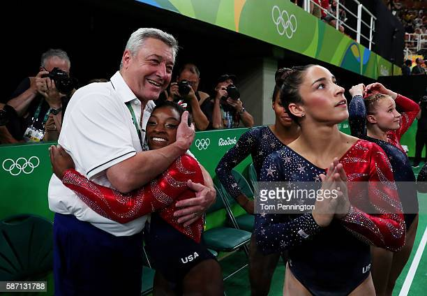 Simone Biles of the United States is embraced by coach Mihai Brestyan after Women's qualification for Artistic Gymnastics on Day 2 of the Rio 2016...