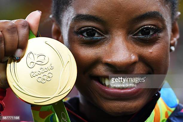 Simone Biles of the United States poses for photographs with her gold medal after the medal ceremony for the Artistic Gymnastics Women's Team on Day...