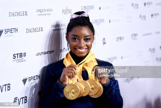 Simone Biles of The United States poses for photos with her multiple gold medals during day 10 of the 49th FIG Artistic Gymnastics World...