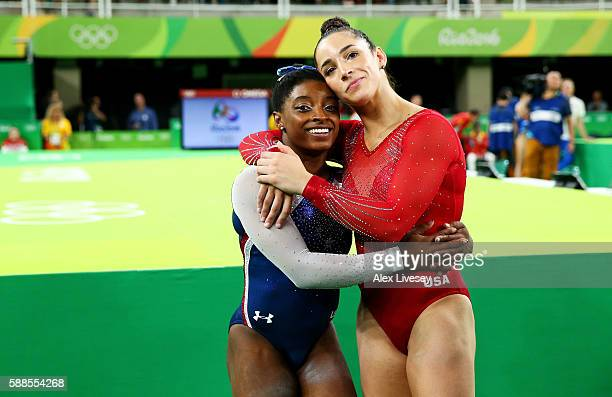 Simone Biles of the United States waits for the score after competing on the floor with Alexandra Raisman during the Women's Individual All Around...