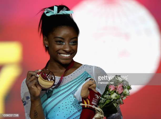 Simone Biles of the USA poses for a photograph with her gold medal after winning the Women's AllRound Final during day eight of the 2018 FIG Artistic...
