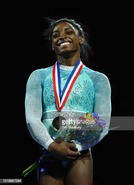 Simone Biles stands on the podium after winning her record fifth US allaround title during day four of the US Gymnastics Championships 2018 at TD...