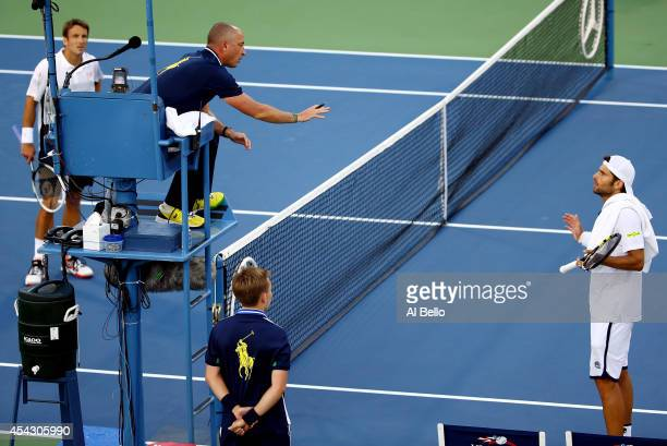 Simone Bolelli of Italy argues a call with the chair umpire as Tommy Robredo of Spain looks on during their men's singles second round match on Day...