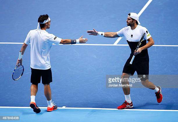 Simone Bolelli of Italy claps hands with Fabio Fognini of Italy in their men's doubles match against Rohan Bopanna of India and Florin Mergea of...