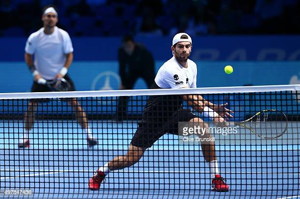 Simone Bolelli of Italy plays a forehand partnering Fabio Fognini of Italy in their men's doubles match against Rohan Bopanna of India and Florin...