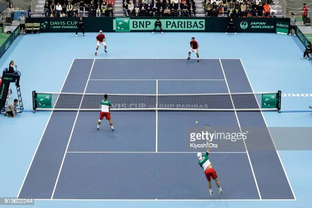 Simone Bolelli of Italy serves as he plays with Fabio Fognini of Italy during their doubles match against Ben McLachlan and Yasutaka Uchiyama of...