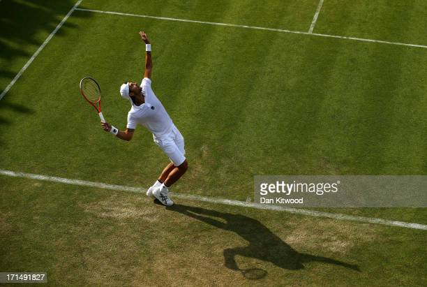 Simone Bolelli of Italy serves during his Gentlemen's Singles first round match against Grigor Dimitrov of Bulgaria on day two of the Wimbledon Lawn...