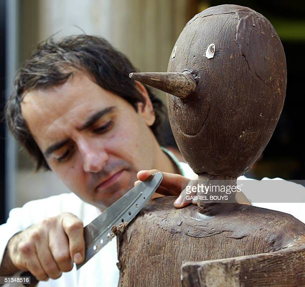 Simone De Castro sculptor from Montopoli works on a chocolate sculpture of Pinocchio during the Eurochocolate 2002 festival 23 October 2002 in...
