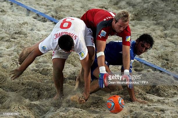 Simone Del Mestre and Matteo Marrucci of Italy and Dejan Stankovic of Switzerland battle for the ball during the FIFA Beach Soccer World Cup Group A...