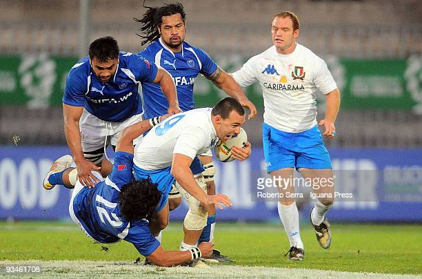 Simone Favaro of Italy is tackled by Seilala Mapusua of Samoa during the friendly match between Italy and Samoa at Stadio Cino e Lillo Del Duca on...