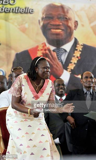 Simone Gbagbo the wife of incumbent Ivorian president Laurent Gbagbo dances under a portrait of her husband during a meeting in his support on...