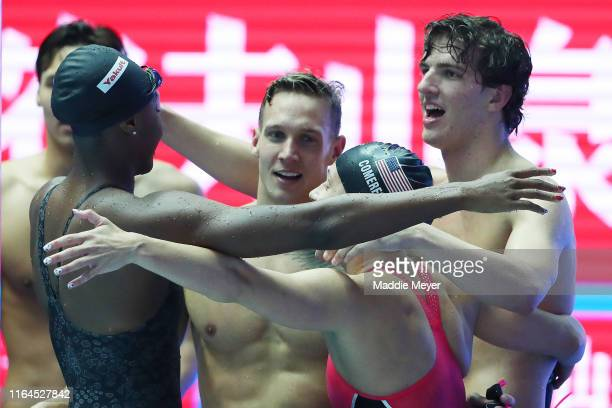 Simone Manuel, Caeleb Dressel, Mallory Comerford and Zach Apple of the United States celebrate after setting a new world record of 3:19.40 in the...