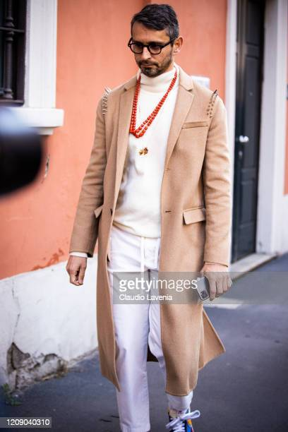 Simone Marchetti, wearing a cream sweater, white pants, red necklace and beige coat, is seen outside Tod's show, during Milan Fashion Week...