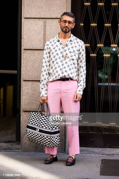 Simone Marchetti wearing a floral print shirt pink trousers Gucci loafers and Dior tote bag is seen outside Giorgio Armani show during the Milan...