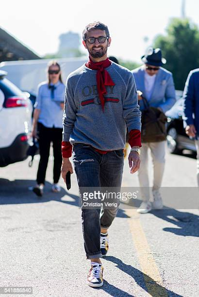 Simone Marchetti wearing a grey sweater and a black denim jeans and red scarf outside Diesel during the Milan Men's Fashion Week Spring/Summer 2017...