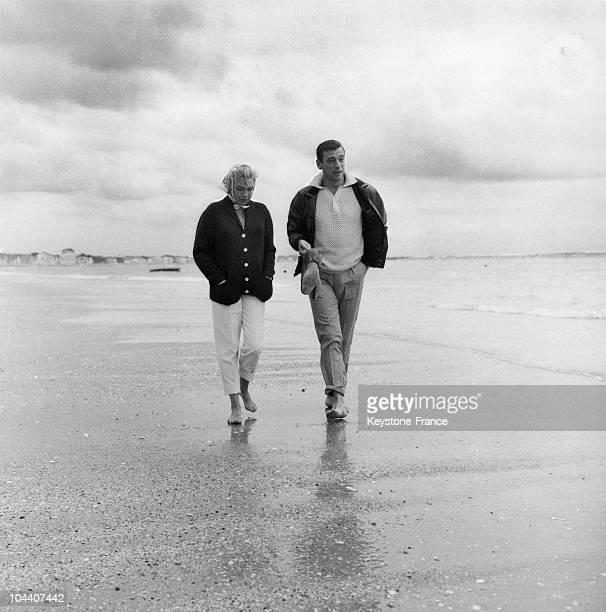Simone SIGNORET and his husband Yves MONTAND walking along the beach at La Baule