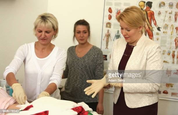 Simone Thiedecke caregiver instructor shows Family Minister Franziska Giffey how to replace a catheter bandage on a training dummy as Giffey visits a...