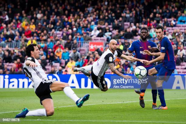 Simone Zaza and Daniel Parejo of Valencia CF try to score during the La Liga match between Barcelona and Valencia at Camp Nou on April 14 2018 in...