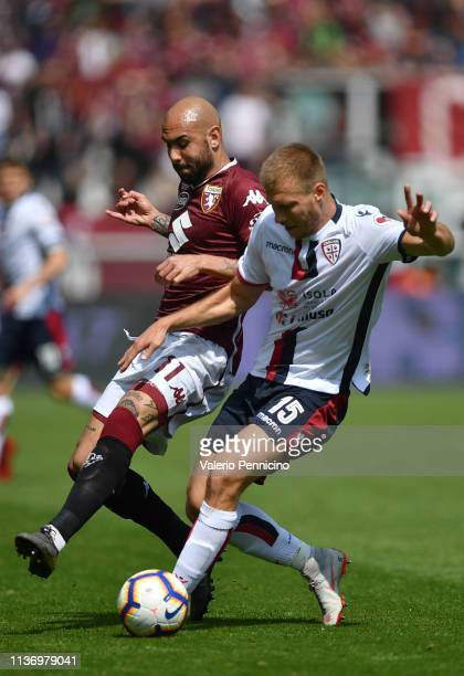 Simone Zaza of Torino FC is challenged by Ragnar Klavan of Cagliari during the Serie A match between Torino FC and Cagliari at Stadio Olimpico di...