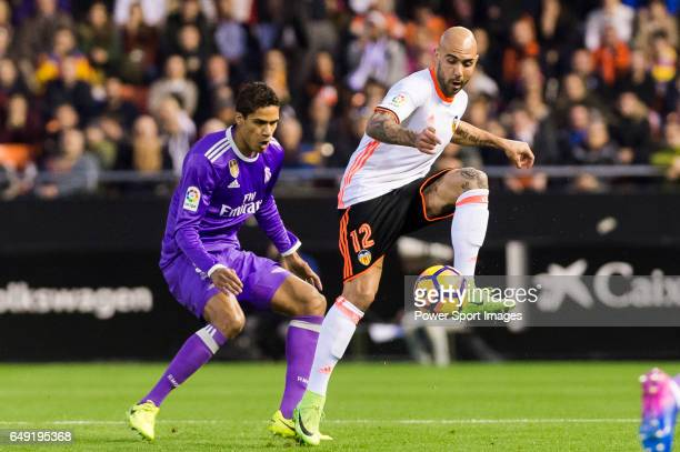 Simone Zaza of Valencia CF competes for the ball with Raphael Varane of Real Madrid during their La Liga match between Valencia CF and Real Madrid at...