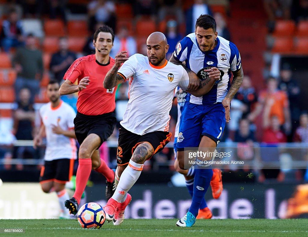 Simone Zaza (L) of Valencia competes for the ball with Joselu Sanmartin of Deportivo de La Coruna during the La Liga match between Valencia CF and Deportivo de La Coruna at Mestalla Stadium on April 2, 2017 in Valencia, Spain.