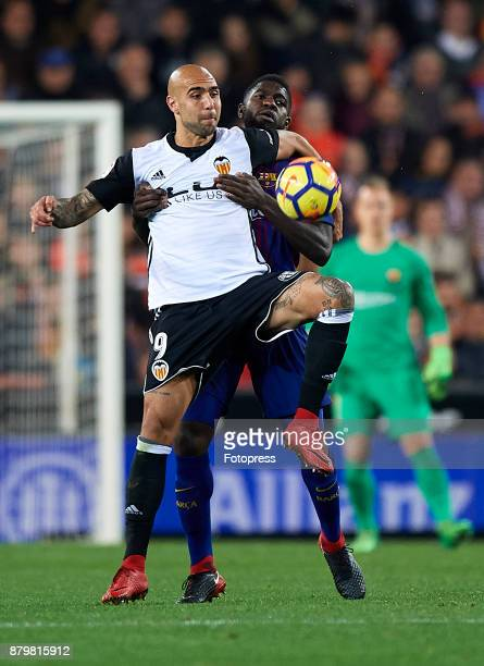 Simone Zaza of Valencia competes for the ball with Samuel Umtiti of Barcelona during the La Liga match between Valencia and Barcelona at Estadio...