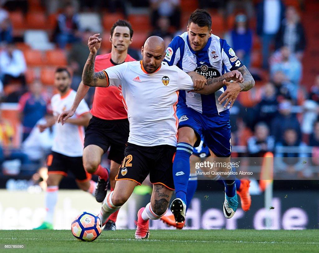 Simone Zaza (L) of Valencia is tackled by Joselu Sanmartin of Deportivo de La Coruna during the La Liga match between Valencia CF and Deportivo de La Coruna at Mestalla Stadium on April 2, 2017 in Valencia, Spain.
