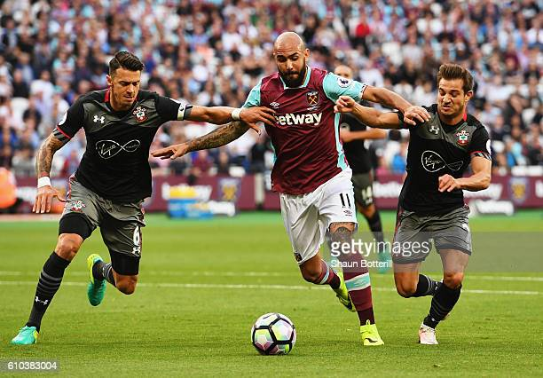 Simone Zaza of West Ham United tangles with Jose Fonte and Cedric Soares of Southampton during the Premier League match between West Ham United and...