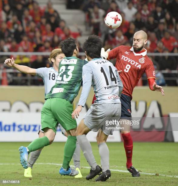 Simovic of Nagoya Grampus vies for the ball against Avispa Fukuoka's Masashi Kamekawa goalkeeper Rikihiro Sugiyama and Takehiro Tomiyasu in the...