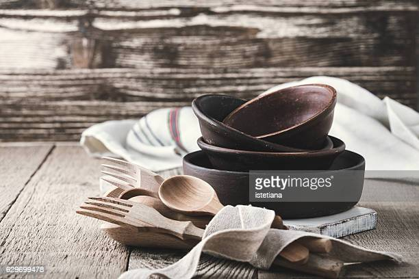 Simple crockery and wooden cooking utensils set on rustic table