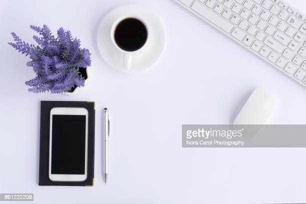 Simple Office Desk With Smart Phone, Coffee, Pen, Keyboard and Flower on White