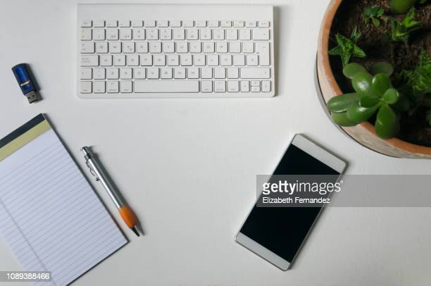 simple office desk with smart phone, keyboard, pen, note pad, pendrive and succulent plants on white background - iphone mockup stock pictures, royalty-free photos & images