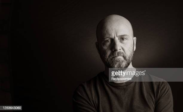 simple studio portrait of a bald man with a beard looking into the camera with a distant vague expression.  black background easy to extend for copy. - black and white stock pictures, royalty-free photos & images
