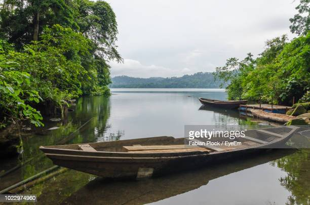 simple wooden boats moored in barombi mbo crater lake against cloudy sky, cameroon, africa - cameroun photos et images de collection