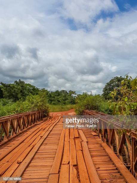 simple wooden bridge amidst trees against cloudy sky in rural gabon, africa - gabon stock pictures, royalty-free photos & images