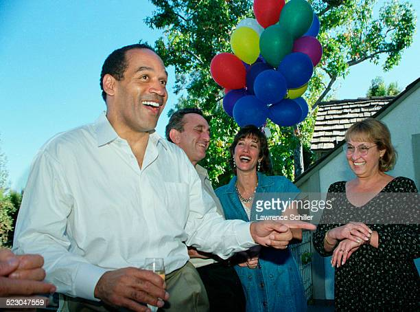 J Simpson after his acquittal at home in Brentwood with friends including his secretary Kathy Randa in the black dress