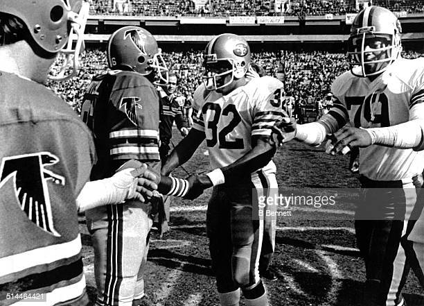 Simpson and Al Cowlings of the San Francisco 49ers greet Jim Mitchell and Greg Brezina of the Atlanta Falcons on December 16, 1979 at Atlanta-Fulton...