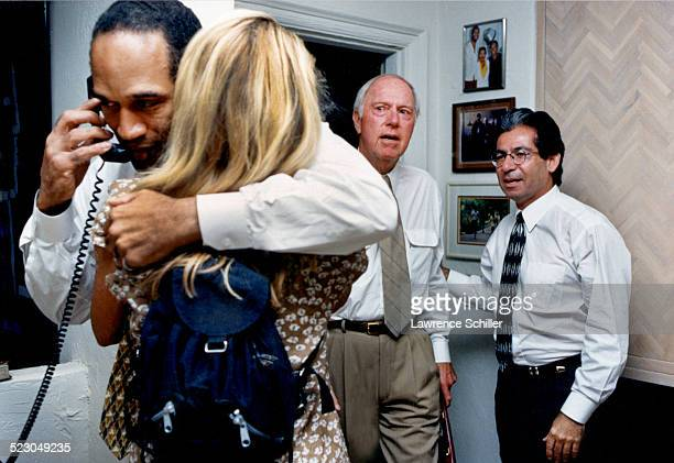 O.J. Simpson, arriving at his home in Brentwood, after his acquittal, with Skip Taft, his attorney in background, and Robert Kardashian on the right.